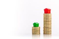 Pilhas de moedas com casa verde e vermelha fotografia de stock royalty free