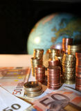 Pilhas de moedas do euro e do centavo na frente de um globo Fotos de Stock Royalty Free