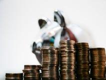 Pilhas de moedas dos pesos colombianos com um mealheiro de prata no fundo que olha ao lado imagem de stock royalty free