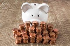 Pilhas de moedas e do mealheiro branco Imagem de Stock