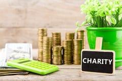 Pilhas de moedas e notas de dólar, calculadora, quadro-negro com texto & x22; CHARITY& x22; imagem de stock