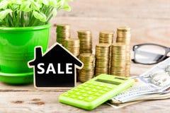 Pilhas de moedas e notas de dólar, calculadora, quadro-negro na forma de uma casa com texto & x22; SALE& x22; imagens de stock