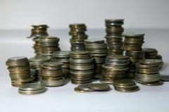 Pilhas de moedas em um fundo branco Imagens de Stock