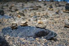 Pilhas de pedra em um litoral rochoso Fotos de Stock Royalty Free