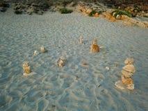 Pilhas de pedras na areia da praia fotografia de stock