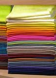 Pilhas de tippets coloridos dos xailes em uma prateleira Foto de Stock