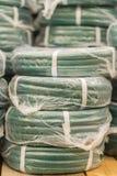 pilhas de tubulação plástica amarela do pvc dos rolos no contador na loja Mangueiras da venda no jardim de vários fabricantes, em foto de stock royalty free