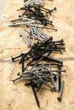 Pilhas de vários pregos e parafusos para o woodworking Fotografia de Stock
