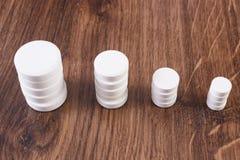 Pilhas dos comprimidos e das cápsulas médicos brancos, conceito dos cuidados médicos fotos de stock