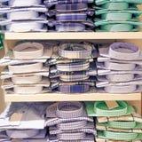 Pilhas masculinas dos t-shirt no prateleiras na loja imagens de stock