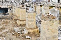 Pilhas poderosas de uma fundação com o rebar de projeção no fundo de uma construção industrial arruinada imagem de stock