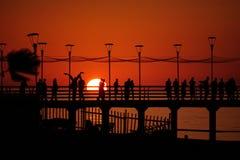 Pilier avec des personnes détendant par le coucher du soleil Photo libre de droits