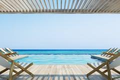 Pilier avec les chaises de plate-forme blanches près d'une piscine Images stock