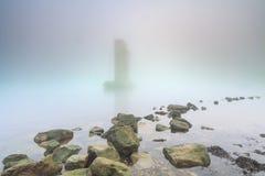 Pilier d'une barrière de montée subite de tempête en brouillard pendant le coucher du soleil photos stock