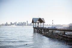 Pilier dans l'eau donnant sur le centre ville de Vancouver Photos libres de droits