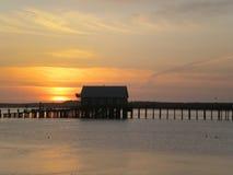 Pilier de baie au coucher du soleil Image stock