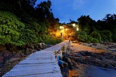 Pilier de bateau et petite maison la nuit Photos stock
