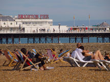 Pilier de Brighton avec des gens détendant sur la plage Images libres de droits