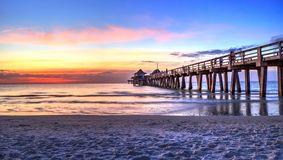 Pilier de Naples sur la plage au coucher du soleil image stock