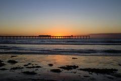Pilier de plage d'océan au coucher du soleil images libres de droits