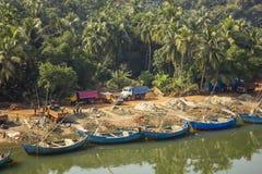 Pilier de rivière avec les bateaux vides bleus le fond de la jungle verte de paume et sable de chargement dans images libres de droits