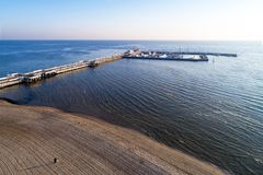 Pilier en bois avec la marina dans la station de vacances de Sopot, Pologne Silhouette d'homme se recroquevillant d'affaires Photographie stock libre de droits