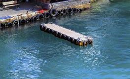 Pilier en bois de rivière pour de petits bateaux avec les pneus utilisés comme pare-chocs Image stock