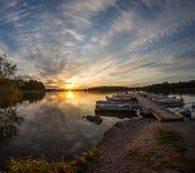 Pilier en bois et un bateau sur un coucher du soleil de lac Image libre de droits