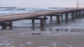 Pilier en bois rouillé sur la plage Vagues de tempête en mer, beau paysage marin au coucher du soleil banque de vidéos