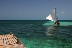 Pilier et bateau de navigation en bois, tabac Caye, Belize Image stock