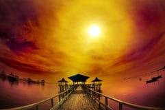 Pilier et océan exotiques sous le lever de soleil nuageux Photos stock