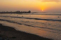 Pilier et plage de Huanchaco au coucher du soleil, Pérou photographie stock