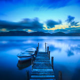 Pilier ou jetée en bois et un bateau sur un coucher du soleil de lac Versilia Tusca Photo libre de droits