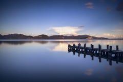 Pilier ou jetée en bois sur une réflexion bleue de coucher du soleil et de ciel de lac dessus Photographie stock