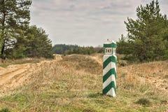Pilier rayé vert et blanc en bois de frontière dans le réseau de quart de forêt de point de repère de forêt de pin Photos stock