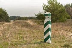 Pilier rayé vert et blanc en bois de frontière dans le réseau de quart de forêt de point de repère de forêt de pin Image libre de droits