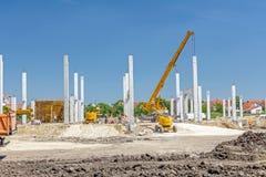 Piliers concrets de nouvel édifice sur la terre arénacée photos libres de droits