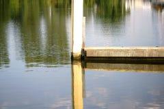 Piliers en acier reflétés sur la rive Photos libres de droits