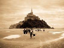 Piligrims walking to Mont Saint Michel stock photo