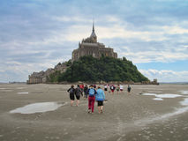Piligrims walking to Mont Saint Michel royalty free stock photo