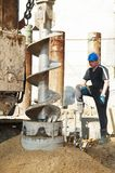 Piling construction works. Worker controlling piling process tube in metal form for continuous concrete casting stock photos