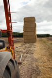 Piling hay bales on a summers day Stock Photo