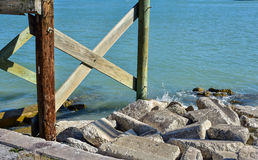 Pilings from pier and rocks Royalty Free Stock Photos