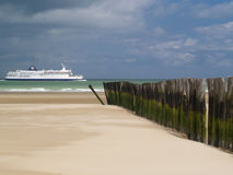 Pilings pointing to ferry. Row of pilings on beach pointing to ferry at sea, Calais, France Stock Photo