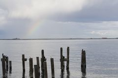 Pilings and rainbow Stock Images