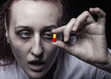 Pill. Young woman holding a pill addict. Focus on hands Stock Image