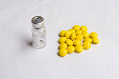 Pill and ampul. Yellow pills and empty ampul in white background Stock Photos