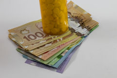 Pill bottle and Canadian Money Hundreds Stock Image
