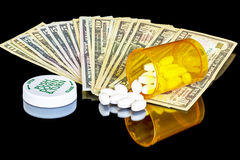 Pill bottle and cold hard cash Royalty Free Stock Images