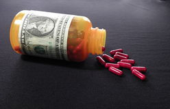Pill Bottle with Dollar Script. Pill bottle with red pills outpoured wraped in dollar bill Stock Image